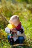 Muchacha del niño con la hoja amarilla Fotografía de archivo libre de regalías