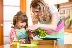 Muchacha del niño con la mamá que cocina pescados en la cocina Imágenes de archivo libres de regalías