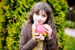 Muchacha del niño con la manzana grande Imagenes de archivo