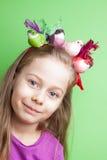 Muchacha del niño con los pájaros coloridos en su cabeza en verde Foto de archivo libre de regalías