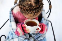 Muchacha del niño con una taza de té caliente al aire libre imagenes de archivo