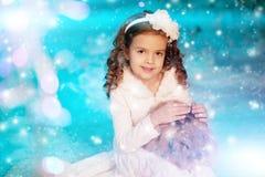 Muchacha del niño de la Navidad en el fondo del árbol del invierno, nieve, copos de nieve Imágenes de archivo libres de regalías