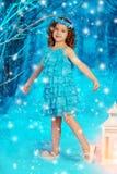Muchacha del niño de la Navidad en el fondo del árbol del invierno, nieve, copos de nieve Imagen de archivo libre de regalías