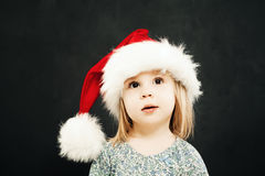 Muchacha del niño de la Navidad en Santa Hat Dreaming fotos de archivo
