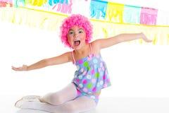 Muchacha del niño del niño con la expresión divertida de la peluca del rosa del payaso del partido Foto de archivo libre de regalías