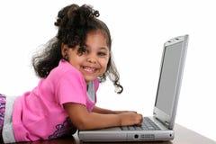 Muchacha del niño en color de rosa con la computadora portátil Foto de archivo