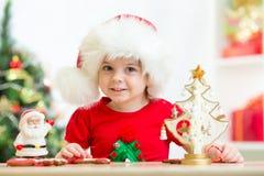 Muchacha del niño en el sombrero de Papá Noel con las galletas de Navidad Imagen de archivo libre de regalías