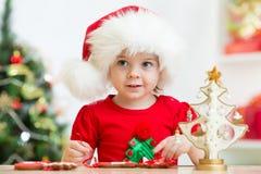Muchacha del niño en el sombrero de Papá Noel que hace la Navidad Imagenes de archivo