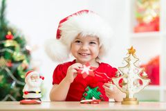 Muchacha del niño en el sombrero de Papá Noel que sostiene las galletas de la Navidad Foto de archivo libre de regalías