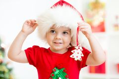 Muchacha del niño en el sombrero de Papá Noel que sostiene las galletas de la Navidad Fotografía de archivo