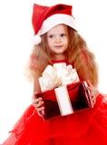 Muchacha del niño en el sombrero rojo de santa con el rectángulo de regalo. Foto de archivo