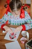 Muchacha del niño en el suéter estacional que sienta y que hace las postales de la Navidad en casa Imagen de archivo libre de regalías
