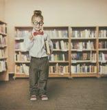 Muchacha del niño en la biblioteca escolar que sostiene los libros, señalando al niño elegante imágenes de archivo libres de regalías