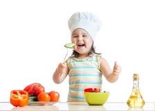 Muchacha del niño en sombrero del cocinero que come verduras Fotografía de archivo