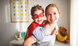 Muchacha del niño en un traje del superhéroe con la máscara y la capa roja Fotografía de archivo libre de regalías