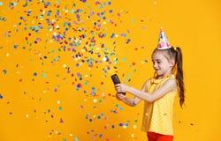 Muchacha del niño del feliz cumpleaños con confeti en fondo amarillo imagen de archivo libre de regalías