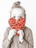 Muchacha del niño joven que lleva a cabo símbolo rojo del corazón - ame el concepto Fotografía de archivo libre de regalías