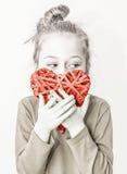 Muchacha del niño joven que lleva a cabo símbolo rojo del corazón - ame el concepto Fotos de archivo
