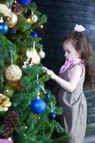 Muchacha del niño que adorna el árbol de navidad para la celebración del Año Nuevo Fotografía de archivo