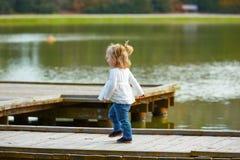 Muchacha del niño que camina en el embarcadero del lago Foto de archivo libre de regalías