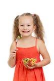 Muchacha del niño que come con los vehículos sanos del alimento Foto de archivo libre de regalías