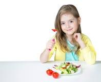 Muchacha del niño que come la ensalada en la tabla aislada en blanco foto de archivo