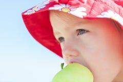 Muchacha del niño que come la manzana Fotos de archivo libres de regalías