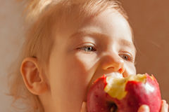 Muchacha del niño que come la manzana roja grande Foto de archivo