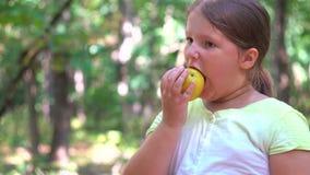 Muchacha del niño que come una manzana roja en un parque en naturaleza almacen de video