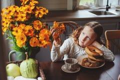 Muchacha del niño que desayuna en casa en mañana del otoño Interior moderno acogedor de la vida real en casa de campo Fotografía de archivo libre de regalías