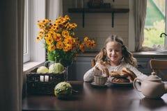 Muchacha del niño que desayuna en casa en mañana del otoño Interior moderno acogedor de la vida real en casa de campo Imágenes de archivo libres de regalías