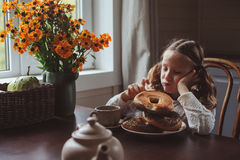 Muchacha del niño que desayuna en casa en mañana del otoño Interior moderno acogedor de la vida real en casa de campo Imagenes de archivo