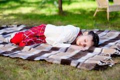 Muchacha del niño que duerme en la tela escocesa en un jardín Imagen de archivo