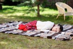 Muchacha del niño que duerme en la tela escocesa en un jardín Imagen de archivo libre de regalías