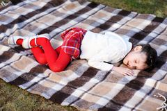 Muchacha del niño que duerme en la tela escocesa en un jardín Imágenes de archivo libres de regalías