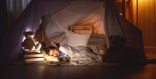 Muchacha del niño que duerme en tienda con el libro y la linterna fotos de archivo
