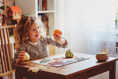 Muchacha del niño que hace el herbario en casa, artes estacionales del otoño Foto de archivo