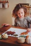 Muchacha del niño que hace el herbario en casa, artes estacionales del otoño Imagenes de archivo