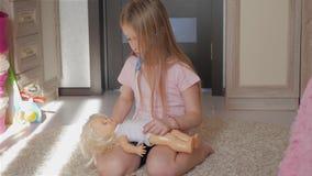 Muchacha del niño que juega al doctor con su muñeca en sitio almacen de video