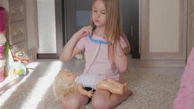 Muchacha del niño que juega al doctor con su muñeca en sitio metrajes