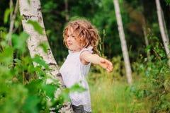Muchacha del niño que juega con el árbol de abedul en bosque del verano Foto de archivo libre de regalías