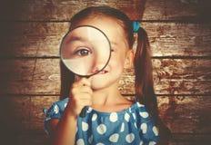 Muchacha del niño que juega con la lupa en detective Imagen de archivo libre de regalías