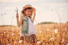 Muchacha del niño que juega con las bolas del soplo en campo del verano Fotos de archivo