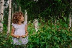 Muchacha del niño que juega con las hojas en bosque del verano con los árboles de abedul Exploración de la naturaleza con los niñ Imagen de archivo