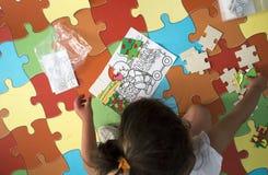 Muchacha del niño que juega con rompecabezas sobre la alfombra del rompecabezas Fotografía de archivo