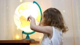Muchacha del niño que juega con un globo iluminado El bebé estudia la geografía y un mapa del mundo metrajes