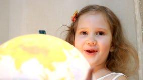 Muchacha del niño que juega con un globo iluminado El bebé estudia la geografía y un mapa del mundo almacen de video
