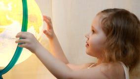 Muchacha del niño que juega con un globo iluminado El bebé estudia la geografía y un mapa del mundo almacen de metraje de vídeo