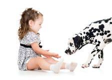Muchacha del niño que juega el perro de perrito Fotos de archivo libres de regalías