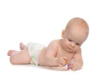 Muchacha del niño que miente con el soother de la entrerrosca del bebé Imagen de archivo